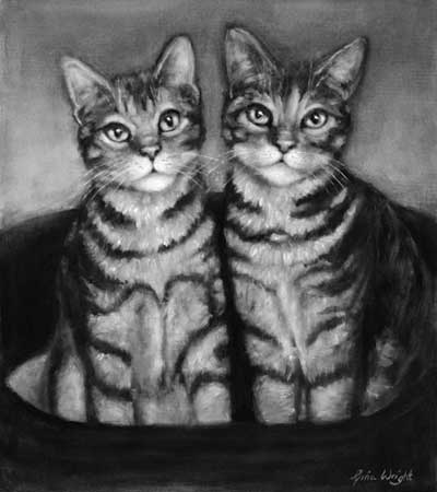 Two tabby cats sitting in their bed