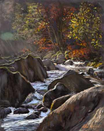 Waterfall on river running between trees in autumn colours
